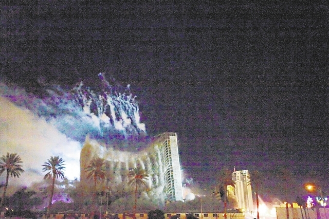 With smoke in the air from the last of the fireworks display, the center of the Stardust hotel-casino folds in on itself as the iconic casino is imploded early Tuesday morning, March 13, 2007, on  ...