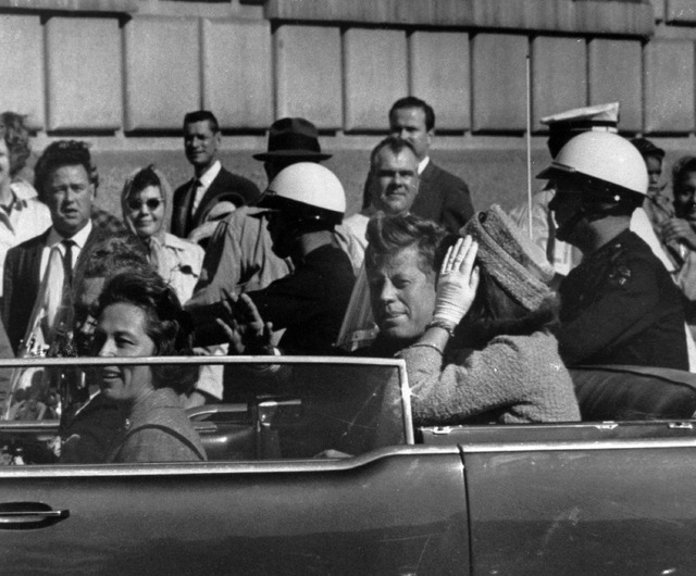 President John F. Kennedy is seen riding in motorcade approximately one minute before he was shot in Dallas, Tx., on Nov. 22, 1963.  In the car riding with Kennedy are Mrs. Jacqueline Kennedy, rig ...