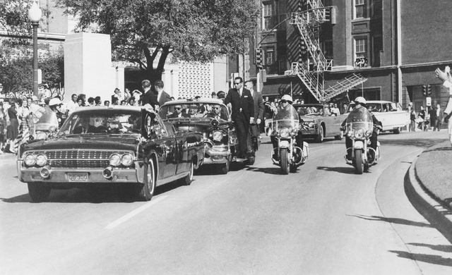 Seen through the limousine's windshield as it proceeds along Elm Street past the Texas School Book Depository, President John F. Kennedy appears to raise his hand toward his head within seconds of ...