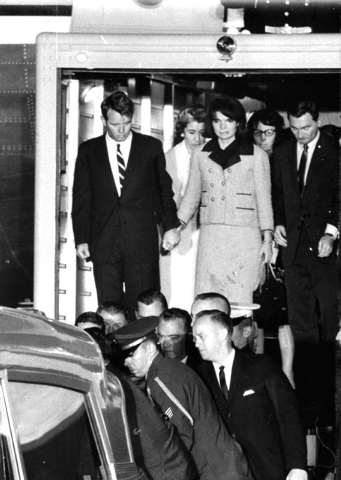 First Lady Jacqueline Kennedy, her dress stained with blood, stands with Attorney General Robert F. Kennedy, holding her hand, as they watch the casket of her slain husband, President John F. Kenn ...