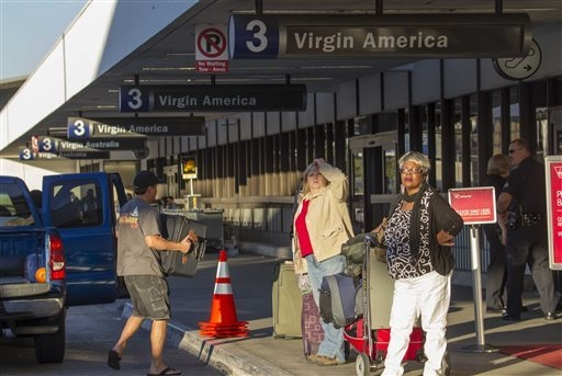 Departing passengers with their luggage arrive on Saturday, Nov. 2, 2013, in Los Angeles International Airport as part of Terminal 3 is reopened after a shooting. A gunman armed with a semi-automa ...