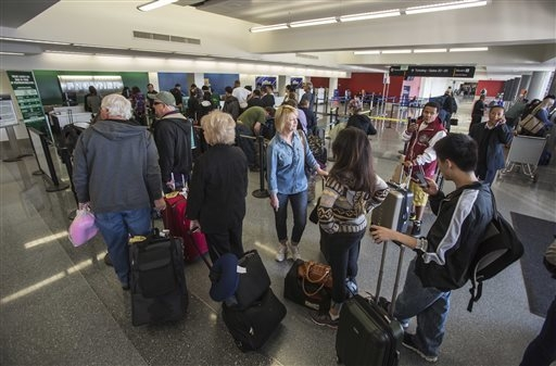 Departing passengers stand in line for check in at Terminal 3 on Saturday, Nov. 2, 2013, in Los Angeles International Airport. A gunman armed with a semi-automatic rifle opened fire at the airport ...