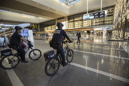 Police officers patrol the Tom Bradley International Terminal on Saturday, Nov. 2, 2013, in Los Angeles. A gunman armed with a semi-automatic rifle opened fire at Los Angeles International Airport ...