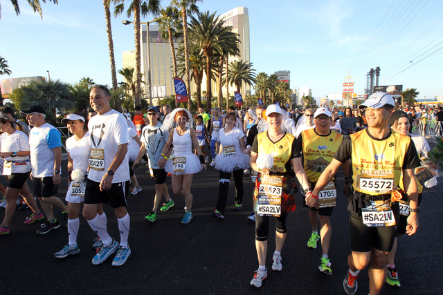 Brides and grooms head to their wedding ceremony before the start of the Rock 'N' Roll Las Vegas Marathon and Half-Marathon on the Strip Sunday, Nov. 17, 2013. (K.M. Cannon/Las Vegas Review-Journal)