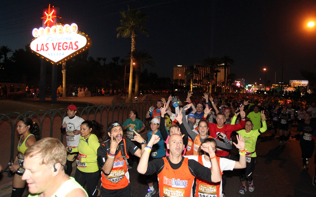 Runners head north and south at the Welcome to Las Vegas sign during the Rock 'N' Roll Las Vegas Marathon and Half-Marathon on the Strip Sunday, Nov. 17, 2013. (K.M. Cannon/Las Vegas Review-Journal)