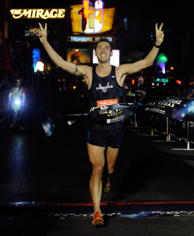 Jason Brosseau of Colorado Spring, Colo., crosses the finish line first in the men's division of the Rock 'N' Roll Las Vegas Marathon on Sunday, Nov. 17, 2013. About 30,000 runners from all 50 sta ...