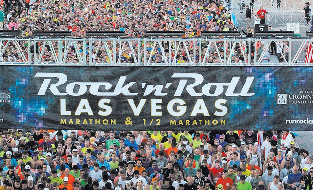Runners cross the starting line at the start of the Rock 'n' Roll Las Vegas Marathon and Half-Marathon on the Las Vegas Strip on Sunday. About 30,000 runners from all 50 states and 52 countries pa ...