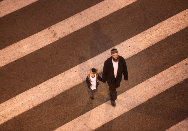 A man and a boy walk across Fourth Street and Fremont Street during the lighting of the menorah on Wednesday, Nov. 27,2013. This year the start of Hanukkah and Thanksgiving overlap. The last time  ...