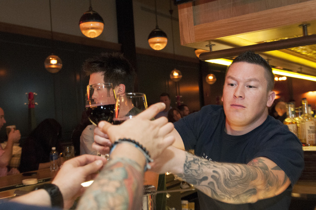 Lee Crain, a bartender at Michael Mina's Pub 1842, hands a couple of wine glasses to a server during dinner service. (Erik Verduzco/Las Vegas Review-Journal)