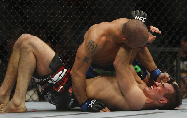Robbie Lawler, top, hits Rory MacDonald during UFC 167 at the MGM Grand Garden Arena in Las Vegas on Nov. 16, 2013. (Jason Bean /Las Vegas Review-Journal)