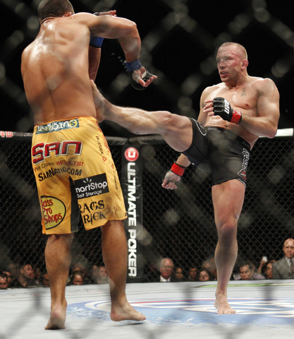 Georges St. Pierre, right, kicks Johny Hendricks during UFC 167 at the MGM Grand Garden Arena in Las Vegas on Nov. 16, 2013. (Jason Bean /Las Vegas Review-Journal)
