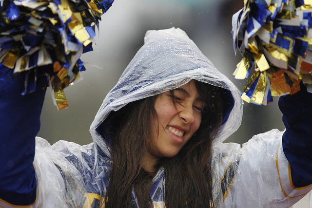 Pahranagat Valley cheerleader Laetitia Ray squints her eyes as rain drops shake off of her pom poms during the division IV Nevada State Football championship game against Spring Mountain in Indian ...
