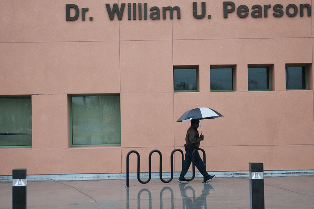 A man walks with an umbrella to William U. Pearson Community Center in North Las Vegas, Saturday, Nov. 23, 2013. The center was named after longtime community activist and politician Dr. William U ...