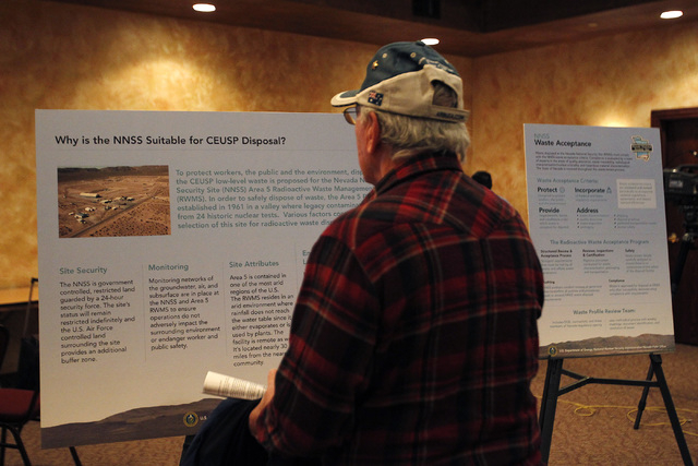 Phil Raneri investigates informational posters before the start of a U.S. Department of Energy public input meeting regarding the plan to relocate uranium waste to the Nevada National Security Sit ...