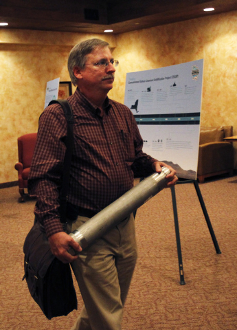 Federal Project Director for Oak Ridge National Laboratory Projects William G. McMillan carries a CEUSP canister into a U.S. Department of Energy public information meeting regarding the plan to r ...