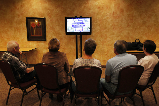 People watch an informational video before the start of a U.S. Department of Energy public input meeting regarding the plan to relocate uranium waste to the Nevada National Security Site at the Ne ...