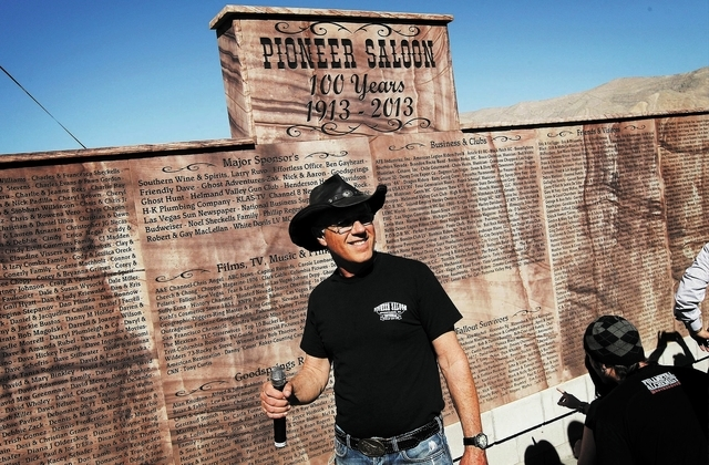 Owner Noel Sheckells unveils a new monument commemorating the 100th birthday of the Pioneer Saloon in Goodsprings on Oct. 19. (Jason Bean/Las Vegas Review-Journal)