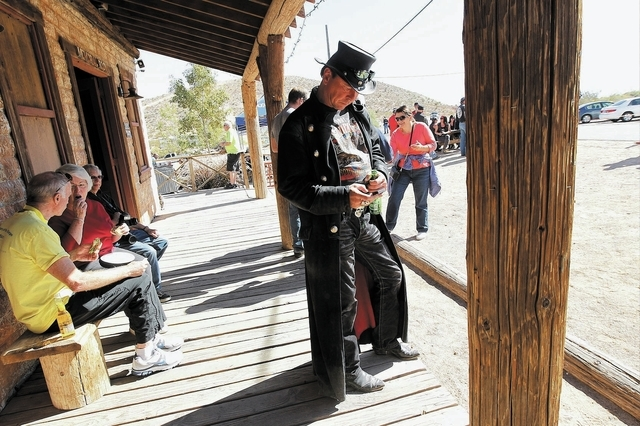 """Patron Soeren """"Z"""" Joensson, middle, checks his cell phone while enjoying a beer during the 100th birthday celebration for the Pioneer Saloon in Goodsprings on Oct. 19. (Jason Bean/Las Vegas Review ..."""