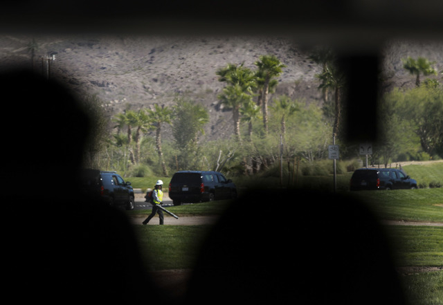A motorcade containing President Barack Obama passes a landscaper at the front entrance of Lake Las Vegas  Monday, Oct. 1, 2012. Obama made surprised visit to the  Obama for America field office i ...
