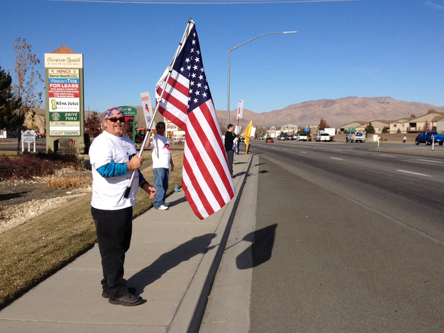 Mark Ransom, of Fernley, waves to traffic with about two dozen protestors in Carson City on Thursday, Nov. 14, 2013, seeking the repeal, or at least delay, of the new health care law. (Sean Whaley ...