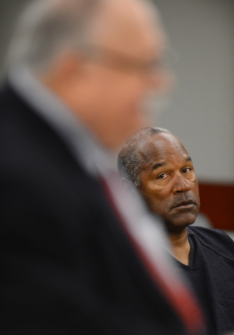 O.J. Simpson looks over at his lawyer Tom Pitaro during an evidentiary hearing in Clark County District Court on May 17, 2013 in Las Vegas. Simpson, who is currently serving a nine-to-33-year sent ...