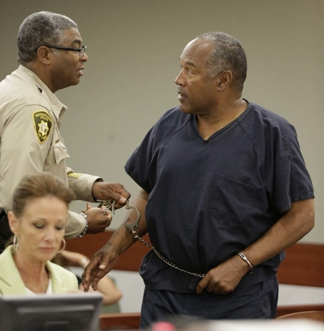 Clark County corrections officer George Gafford, left, uncuffs the right hand of O.J. Simpson after a break during an evidentiary hearing in Clark County District Court, Thursday, May 16, 2013 in  ...