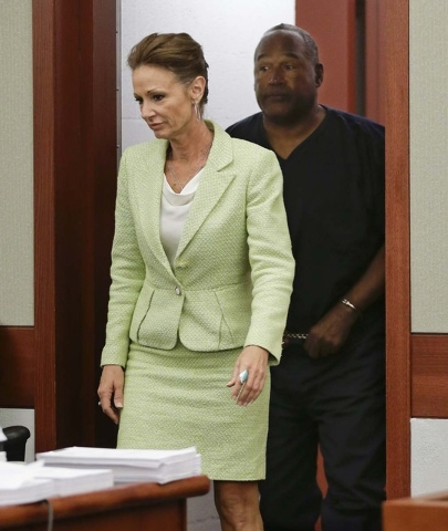 O.J. Simpson, right, returns to the courtroom behind his attorney Patricia Palm after a break during an evidentiary hearing in Clark County District Court, Thursday, May 16, 2013 in Las Vegas. Sim ...