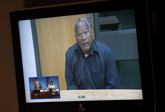O.J. Simpson, in custody at the Lovelock Correctional Center, appears before the Nevada Board of Parole via video conference, in Carson City, Nev., on Thursday, July 25, 2013.  (Cathleen Allison/L ...