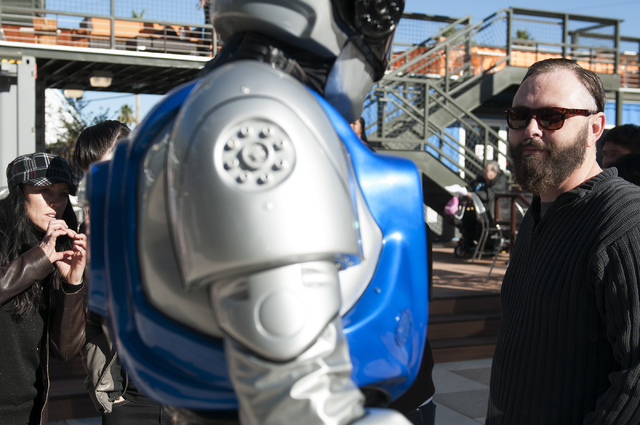 Visitor Ken Osborne, right, watches a man in a robot suit as he welcomes visitors to the Container Park in downtown Las Vegas during its opening Monday, Nov. 25, 2013. (Erik Verduzco/Las Vegas Rev ...