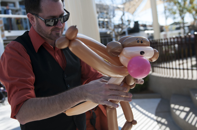 Entertainer Kris Cope makes a monkey ballon hat for a child at the Container Park in downtown Las Vegas during its opening Monday, Nov. 25, 2013. (Erik Verduzco/Las Vegas Review-Journal)