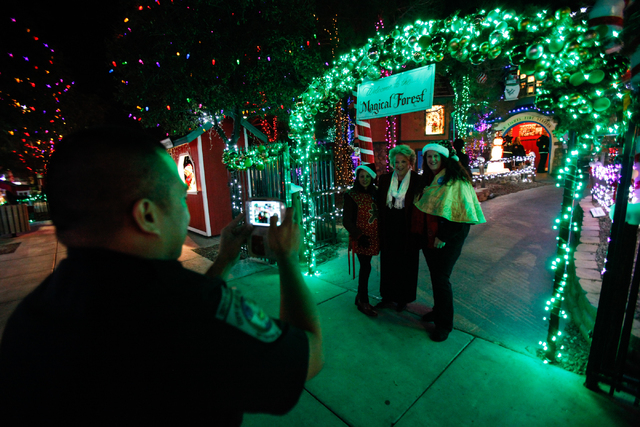 Deputy City Marshal Kevin Punzalan, left, takes a photo of Las Vegas Mayor Carolyn Goodman, center, with volunteers Patricia Francheteau, left, and Debbie Damron, at the Magical Forest at Opportun ...
