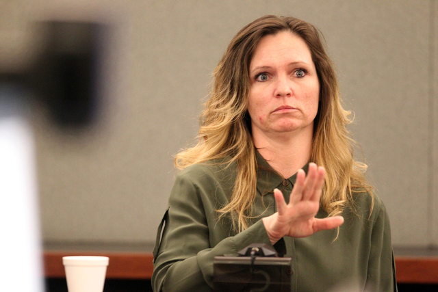 Amy Bessey, who is accused hiring her son and brother to kill her husband, answers questions on the witness stand during her trial at the Regional Justice Center Monday, Nov. 25, 2013. Her estrang ...