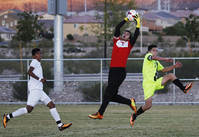Liberty goalie Joey Schibetta reaches up for a save as Green Valley's Roberto Rodriguez (7) races by during their quarterfinal soccer game at Heritage Park in Henderson on Nov. 5, 2013. (Jason Bea ...