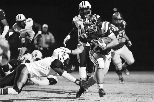 Liberty running back Tyler Parvin (23) breaks free from a Canyon Springs defender during the Sunrise Region semifinal game at home in Henderson, Friday, Nov. 15, 2013. The Liberty Patriots were do ...