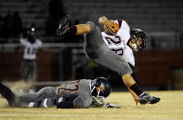 Cimarron-Memorial's Michael Barnson (28) adds a little effort to his run against Legacy's DeMichael Walker during the first half of a high school football game at Legacy High School on Friday, Nov ...