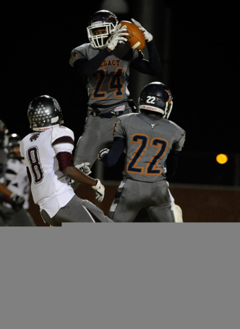 Legacy's Casey Hughes (24) intercepts the ball against Cimarron-Memorial's Maurice Bennett (8) during a high school football game at Legacy High School on Friday, Nov. 1, 2013. Legacy's DeMichael  ...