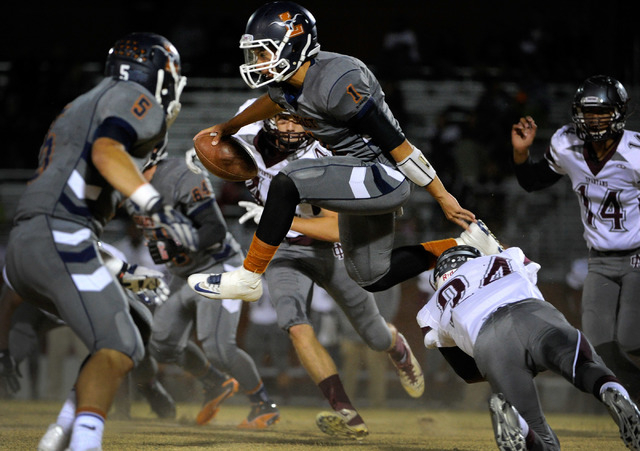 Legacy's quarterback Devin Williams (1) jumps over Cimarron-Memorial's Javon Martin (24) to pick up additional yardage during a high school football game at Legacy High School on Friday, Nov. 1, 2 ...