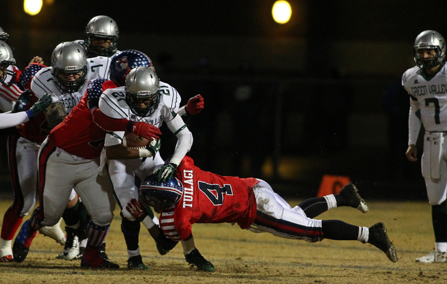 Green Valley's Larry Norman (21) is taken down by Liberty during the Division I Sunrise Region championship game at Liberty High School in Henderson on Friday, Nov. 22, 2013. (Chase Stevens/Las Ve ...
