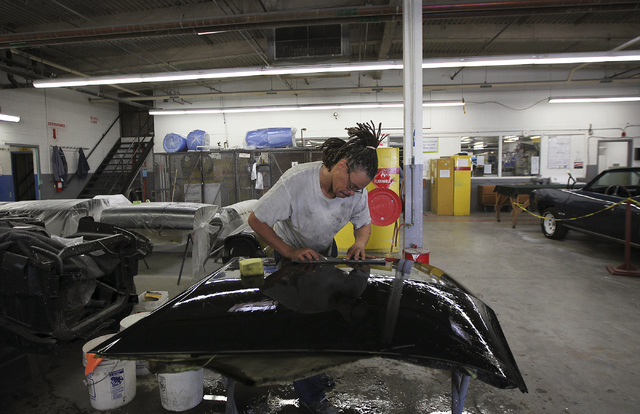 An inmate worker wet sands a hood panel while participating in the car restoration program, operated through Silver State Industries, at the Southern Desert Correctional Center near Indian Springs ...