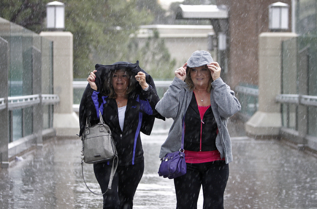 Carol Bradford, left, and Evelyn Downing protect themselves from the rain Thursday as they cross Las Vegas Boulevard on an elevated walkway between Wynn Resorts and Fashion Show Mall. (John Locher ...
