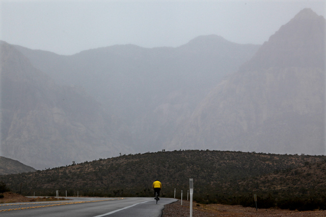 Cyclists ride through the rain near Red Rock Canyon National Conservation Area west of Las Vegas on Thursday. Las Vegas received the first measurable rainfall since September on Thursday and more  ...