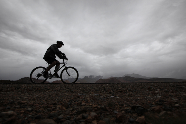 A cyclist ride through the rain near Red Rock Canyon National Conservation Area west of Las Vegas on Thursday. (Justin Yurkanin/Las Vegas Review-Journal)