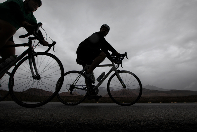 Cyclists ride through the rain near Red Rock Canyon National Conservation Area west of Las Vegas on Thursday. (Justin Yurkanin/Las Vegas Review-Journal)
