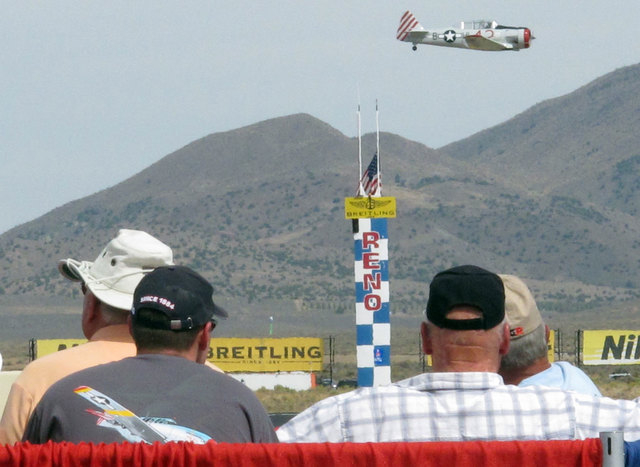 """Fans watch Rob Sandberg of Seattle cross the finish line in his SNJ-4 """"Honest Entry'' in the T-6 class prelims at the Reno National Championship Races on Sept. 14, 2012.  (AP Photo/Scott Sonner)"""