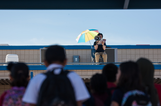"A dressed-up Jaymes Aimetti, principal of Rex Bell Elementary School, reads ""Diary of a Wimpy Kid"" to students from the roof at the school in Las Vegas on Thursday, Nov. 14, 2013. (Chase ..."