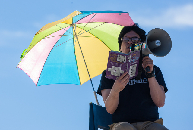 "A dressed-up Jaymes Aimetti, principal of Rex Bell Elementary School, reads ""Diary of a Wimpy Kid"" to students from the roof at the school in Las Vegas on Thursday. (Chase Stevens/Las Vegas Review ..."