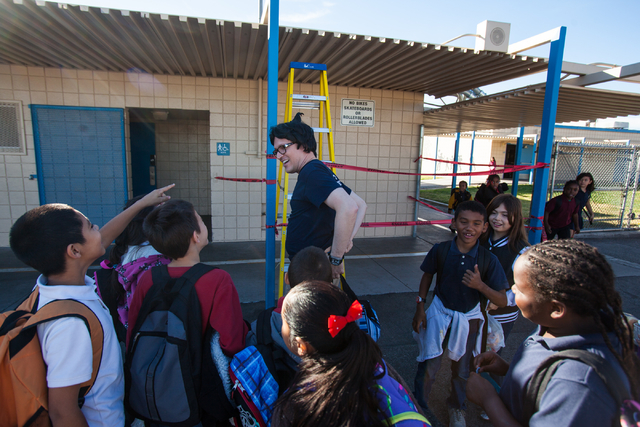 "Students crowd around a dressed-up Jaymes Aimetti, principal of Rex Bell Elementary School, as he prepares to climb on to the roof to read ""Diary of a Wimpy Kid"" to students at the school in Las V ..."