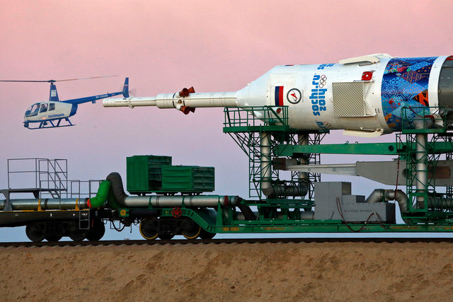 A Russian police helicopter guards the Russia's booster rocket Soyuz-FG with the space capsule that will carry a new crew to the International Space Station as the rocket is transported from hanga ...
