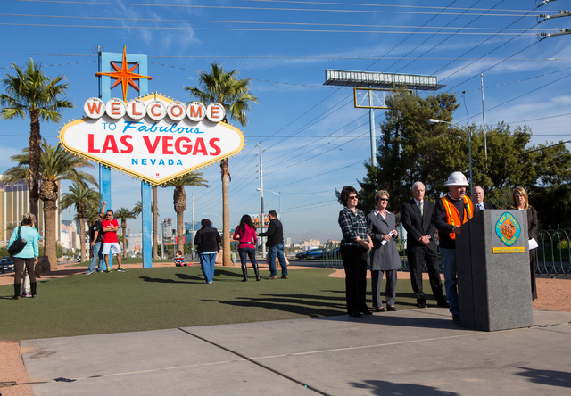 """People have their photos taken in front of the """"Welcome to Fabulous Las Vegas"""" sign while Chris Brooks with Bombard Renewable Energy addresses a crowd from the podium during a groundbrea ..."""
