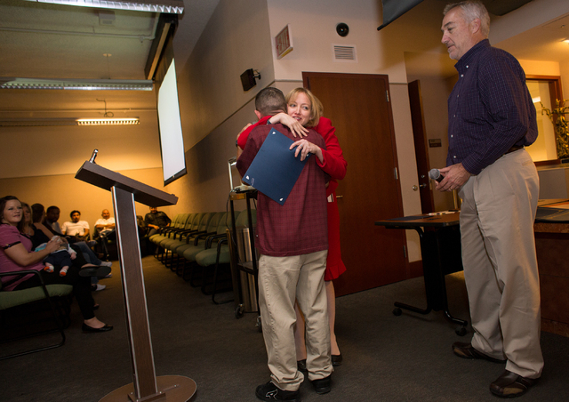 Judge Linda Marie Bell, center, hugs Glenn Porter, a graduate of veterans court, a specialty District Court program, Friday, Nov. 1, 2013 at the Regional Justice Center, located at 200 Lewis Ave.  ...